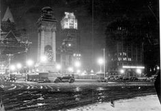 1928  Night scene showing a lighted Clinton Square and the Soldiers and Sailors Monument from the left side of the Square. We see (left to right) the darkened Syracuse Savings Bank, the Chimes Building (also dark), the State Tower Building (lighted) and Onondaga Savings Bank with sign lighted and some offices still lit. Snow on streets and parked cars.  -Schuelke Collection, courtesy of the Liverpool Public Library