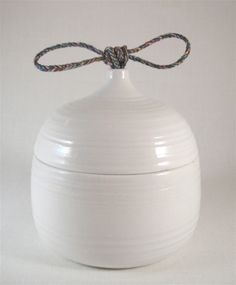 Porcelain with glossy white glaze and multi-color braided thread knot. Len Carella