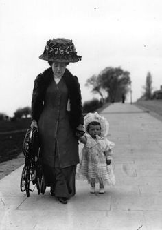 1910: A MOTHER WALKS WITH HER BABY AND HOLDS THE NEW STURGIS BABY CARRIAGE WHICH CAN BE FOLDED UP AND CARRIED.