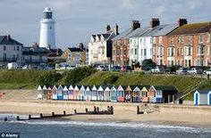 Beautifully painted beach huts, with a typically British lighthouse in the distance.