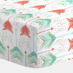 """Coral and Teal Arrows Crib Sheet   Carousel Designs.  Our fitted crib sheets feature deep pockets and have elastic all the way around the edges to hug mattresses securely. Fits standard crib mattresses, measuring approximately 28"""" x 52""""."""