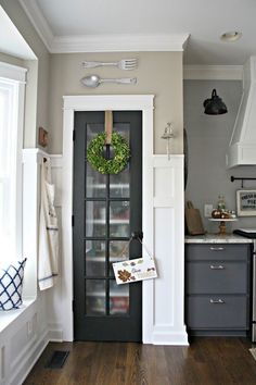 Black glass pantry door kitchen with white trim...