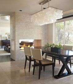 minimalistic decor, but fabulous elements of design (amazing chandelier, X-legged rich wood table, textures, natural lighting, & architecture) with contemporary fireplace linking two spaces and creating ambiance. beautiful!
