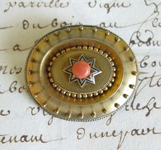 "Beautiful Victorian-era Etruscan gold brooch with a coral center. The brooch is brushed gold with enamel detail and beautiful beading. I have not tested it for solid gold and there are no markings. It measures 2-1/2"" by 2."" It has a loop if you wish to wear as a pendant."