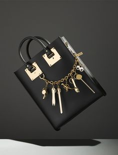 Browse our collection of polished gold-plated charms. Each one designed to be both beautiful and useful, choose your favourites to suspend from our glossy gold charm chain - a personal addition to the Mini Albion Tote in black.