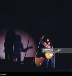Guitarist Jimmy Page (right), of British rock band Led Zeppelin, performing on stage at the Wembley Empire Pool, London, 23rd November 1971. In the shadows on the left are Robert Plant and John Paul Jones.