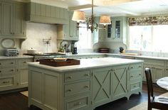 Chic modern French country kitchen with green gray kitchen cabinets & kitchen island, gold marble counter tops & backsplash, beadboard,  brushed nickel pot filler, beadboard ceiling and floral roman shades.