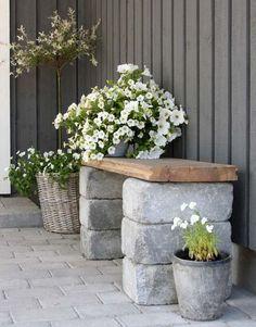 Gartenbank aus großen Steinen und einem Holzbrett:
