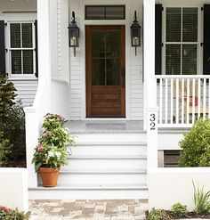 """Sugarberry Cottage -Walk Up    Gas lanterns on either side of the front door are especially inviting at dusk/cocktail hour. """"I consider the front porch the foyer of a Habersham home,"""" Yergens says. ~ maybe have 3 tiers of potted plants for front porch?"""