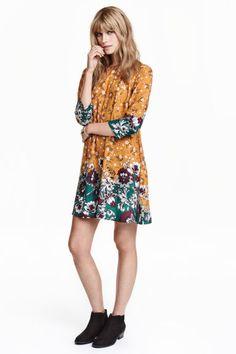 Wzorzysta sukienka: Krótka sukienka o trapezowym kroju z tkaniny we wzorzyste nadruki. Odcinana talia z tyłu, rozszerzany marszczony dół. Na karku rozcięcie z guzikiem. Rękawy 3/4. Bez podszewki.