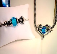 """We have received the 2015 Spring collection from Trollbeads! Seen here on the bangle the, """"Jewel of the Sea"""", two piece silver bead with the Glow-In-The-Dark, """"Sea Glow"""", glass bead. On the necklace the, """"Dolphin Love"""", decor pendant with the, """"Blue Trace"""", glass bead."""