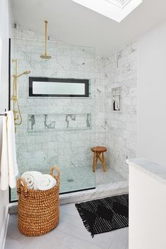 Beautifully designed transitional bathroom features a woven hamper placed on gray wood like floor tiles covered with a black bath mat positioned in front of a walk-in shower fitted with a glass partition and an exposed plumbing brass shower kit fix to marble surround tiles, facing a small niche, and matching a brass rain shower head hung from a sloped ceiling over.