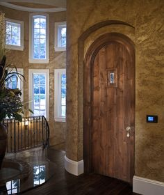 This Tuscan style home has a traditional hallway with dark wood floors and a dark wood rounded door. The window placement brightens the stairway and adds a nice touch to the golden textured walls. Click the image to see how much it costs to replace windows.