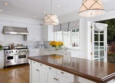 Tish Key Interior Design - Huge open kitchen design with white kitchen cabinets, carrera counters, butcher block island and french doors to the yard
