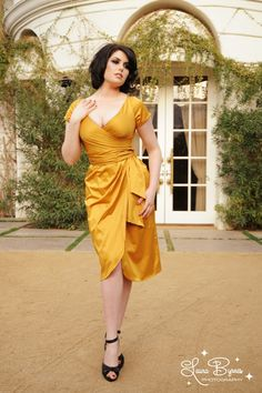 Ava Dress in Burnt Gold - The Ava Dress has now become one of our most popular Pinup Couture styles for everything from a night on the town to bridal parties.  Offered in an array of jewel tones and wedding colors, the Ava is made of a luxurious shakira satin and features a faux wrap front and tulip skirt, back zipper, attached wrap belt, and gorgeous plunging neckline. The result is a cut flattering on just about every body type and suitable for a variety of occasions.