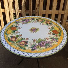Round Italian Volcanic Stone Table with Iron Base – Mixed fruit on orange with crosshatched border. This beautiful and virtually indestructible volcanic aggregate table is harder than granite, is all-weather safe and made to last a lifetime. Expert Italian artisans transform the carved volcanic stone using the same skills developed during centuries of fine ceramic artistry – but these high-fired tables are NOT CERAMIC! They are made to be left outside year 'round – rain, snow or shine – with…