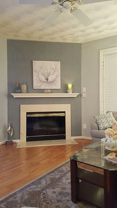 I recently painted the Living Room in shades of gray. Corner fireplace on the accent wall creates a focal point.