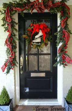 The white skates & red ribbon stand out against the black door