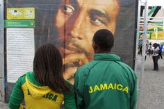 "A young couple decked out in ""Jamaica"" jackets stop at a display honoring reggae icon Bob Marley set up on the grounds of the national stadium in Kingston, Jamaica, Monday, Aug. 6, 2012."