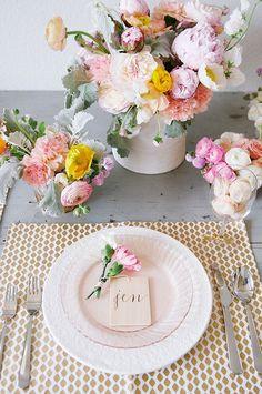 um centro de mesa delicado com flores e um marcador simples