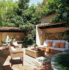 Terraza con un pequeño comedor al fondo y zona de descanso con un banco de obra y butacas de fibras_00248945