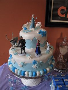 Frozen birthday cake: fondant cake with Cake Boss fondant snowflake cutters, some hand crafted snowflakes, and Disney figurines.