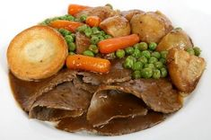 british roast dinner with beef, gravy, carrots, peas, roast potatoes