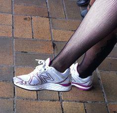 scarpe da tennis bianche indossate con gonna e calze a rete. Per arrivare comodi in ufficio.