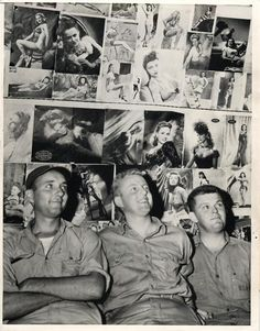 1945- U.S. soldiers of the Naval Air Transport Service on Kwajalein Atoll pose by wall of their quonset hut which has been covered with pin-up girls.