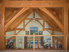 This traditional timber frame's loft area has views of the valley below through the great room windows.