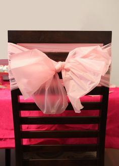 Decorate the chairs with inexpensive plastic table cloths. Cut them into strips and tie around the back of the chairs.