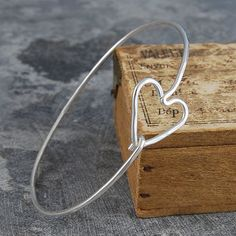 This beautiful classic handmade bangle features a sterling silver 'easy to open' heart motif. This on-trend and modern silvery bracelet jewellery is handmade to perfection. #Otisjaxon #Jewellery #Accessories #Bangle #Women