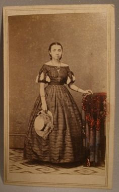 Photograph of girl wearing dress w/ wide neckline and short sleeves (characteristic of younger girls), but with longer skirt length.