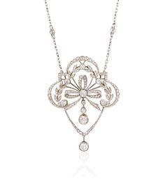 An Edwardian diamond pendant with laurel leaf and bow decoration, in platinum and gold, suspending from a platinum and collet-set diamond chain. Atw 1.53 cts.
