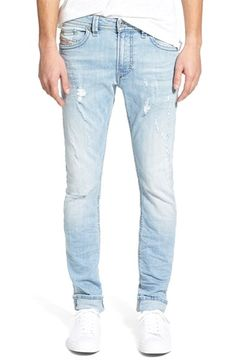 Faded light-blue denim jeans in a streamlined slender fit are amply  distressed with knicks, abrasions and holey knees for a true vintage ...