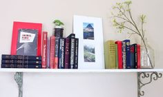Small home library using a shelf lined with classic novels. Click through to read more on this project as well as posts about architecture, interior design and sustainability at www.ofhousesandtrees.com.