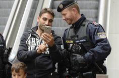 Mann und Polizist schauen auf ein Smartphone