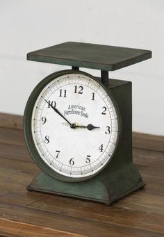 This cute Farmhouse Scale Clock is perfect for decorating small spaces! To bring a bit of vintage charm add this on your counter or open shelving! - Metal - Batteries required - 7x7x9