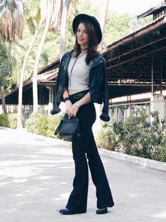 Chapéu e mini bag com cropped (top crop) e calça preta flare com casaco de couro ao estilo boho chic