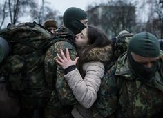 A new volunteer for the Ukrainian Interior Ministry's Azov battalion embraces his girlfriend in Kiev on Saturday before departing to the front lines in eastern Ukraine.