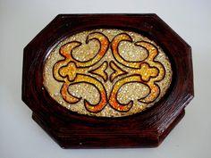 Caixa de madeira, oitavada retangular, com revestimento externo em decapê escuro e tampa trabalhada em vitral. <br>Forrada internamente.