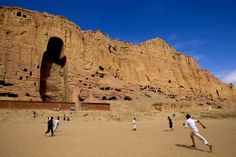 Boys Play football in front of Buddha - Fineart photography by Rada Akbar. The Buddhas of Bamiyan were two 6th century monumental statues of standing buddha carved into the side of a cliff in the Bamiyan valley in the Hazarajat region of central Afghanistan, 230 km (140 mi) northwest of Kabul at an altitude of 2,500 meters (8,202 ft). Built in 507 AD, (smaller), and 554 AD, (larger) the statues represented the classic blended style of Gandhara art.