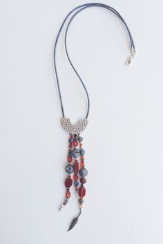 "The Phoenix Tail Necklace, it's length is 21"", it has druzy, carnelian and Sterling silver beads with an antique silver U shaped pendant. Incredibly lightweight metallic silver leather chain. www.flordekaronka.com"