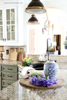 Savvy Southern Style: Copper in the Kitchen and Spring Flowers| French country kitchen| breadboards| copper| collections| blue and white| sage green cabinets| snowfall white Benjamin Moore painted cabinets| brass pendants| industrial| giallo ornamental granite