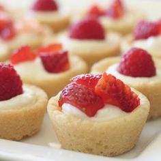Adorable sugar cookie tarts filled with sweetened cream cheese and a berry on top.