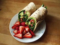 multi-grain wrap with fat free refried beans, guacamole, chipotle salsa, spinach, cucumber, and cherry tomatoes, and sliced strawberries