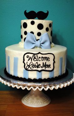 """Mustache baby shower cake. """"Welcome Little Man"""". Frosted in buttercream with fondant accents."""