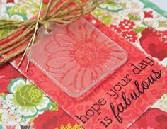 Ellen Hutson:  Frosted-glass-stamping  Sand a plastic tag and stamp with Versamark & clear embossing, heat and voila!  Works best with simpler designed stamps.  Sample is a HA flower.