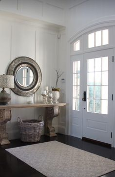 Entryway with arched doorway, white wall paneling, rustic console ...