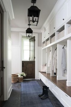 A walnut dutch door flanked by a vertical beadboard trim opens to a blue runner lit by two carriage lanterns hung in front of a white storage bench accented with a wood top fixed beneath open lockers.